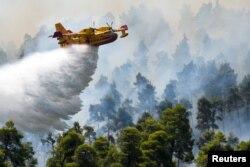 Avião de combate a incêndios despeja água sobre as chamas junto da vila de Ellinika, ilha de Evia, Grécia, 8 Agosto, 2021.