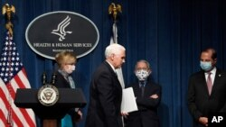 Vice President Mike Pence, second from left, walks off of the stage following the conclusion of a briefing with the Coronavirus Task Force at the Department of Health and Human Services in Washington, Friday, June 26, 2020. Dr. Deborah Birx, left,…