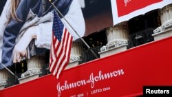 FILE - The U.S. flag is seen over the company logo for Johnson & Johnson to celebrate the 75th anniversary of the company's listing at the New York Stock Exchange (NYSE) in New York, Sept. 17, 2019.