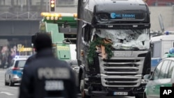 The damaged towing truck is towed away from the crime scene in Berlin, Germany, Tuesday, Dec. 20, 2016, the day after the truck ran into a crowded Christmas market.