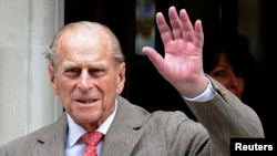 FILE - Britain's Prince Philip waves to members of the media as he leaves the King Edward VII Hospital in London.