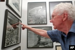 In this June 27, 2019 photo, Gerald Schaber, a former geologist with the U.S. Geological Survey's Astrogeology Science Center, points to a hill on the moon that bears his name in a photograph hanging in his Flagstaff, Ariz., office.