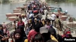 Para pengungsi Muslim Sunni Irak yang meninggalkan kota Ramadi menyeberangi jembatan dan berusaha masuk ke kota Baghdad, Minggu (24/5).