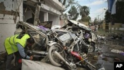 A Pakistani rescue worker examines a wreckage after a bomb blast in Faisalabad, Pakistan on Tuesday, March 8, 2011.