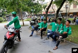GrabBike drivers take a break at a small park in Hanoi, Vietnam, June 21, 2017. Vietnam's motorbike taxis are seeing their business dry up as customers increasingly opt for ride hailing services like Uber and Grab-Taxi.