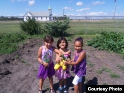 Young members of the Crow Creek community showing the fruits of their gardening labors. Photo courtesy of the Crow Creek Fresh Food Initiative