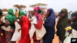 Women wait in line at a food distribution site in Dolo, Somalia, July 18, 2012.