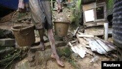 Un hombre saca lodo de una casa en una ladera en Scorpion Alley, Carenage, a unos 10 kilómetros de Puerto Príncipe, Haití, donde las lluvias torrenciales de Isaac han causado algunos daños materiales.