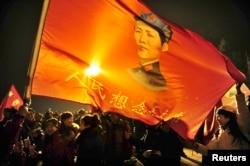"""在韶山,毛泽东的支持者挥舞的旗子上有毛像和标语""""人民想念毛主席""""(2013年12月25日)"""
