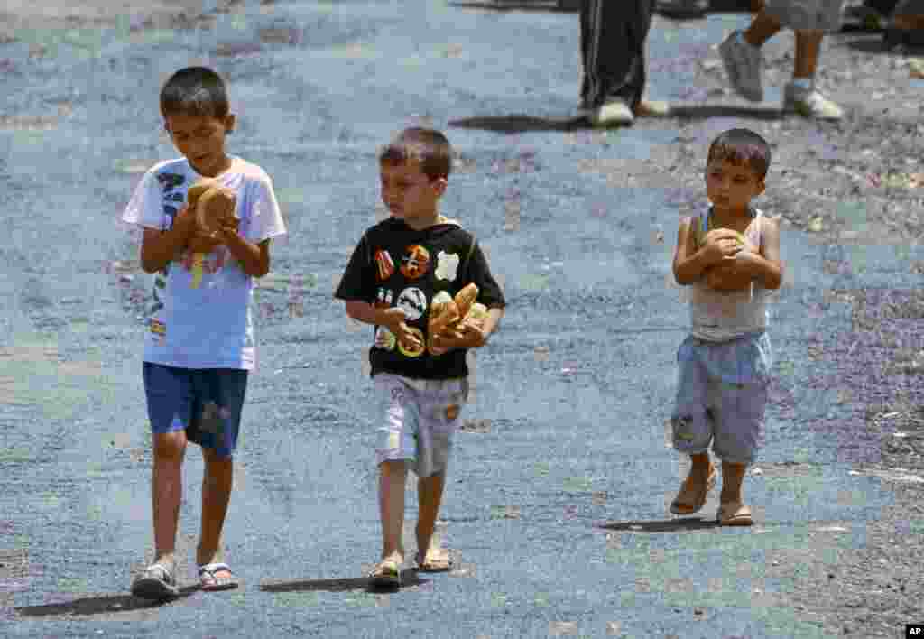 Syrian refugee children carry loaves of bread at a refugee camp in the Turkish border town of Yayladagi, in Hatay province June 27, 2011 (Reuters)