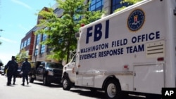 FILE - an FBI evidence response team vehicle is parked outside Building 197 at the Navy Yard in Washington as evidence of a mass shooting is collected, Sept. 18, 2013.