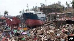 Sebuah kapal tersangkut di atas rumah-rumah yang hancur akibat hantaman topan Haiyan di kota Tacloban, provinsi Leyte, Filipna tengah (10/11).