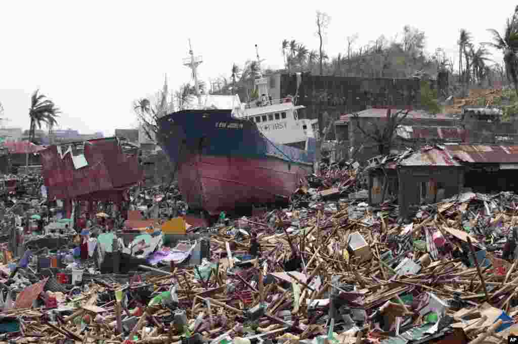 A ship lies on top of damaged homes after it was washed ashore by Typhoon Haiyan in Tacloban city, Leyte province, central Philippines. The city remains littered with debris from damaged homes as many complain of shortages of food and water and no electricity since Typhoon Haiyan slammed into their province.