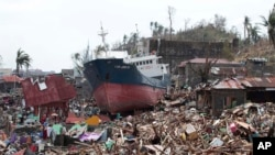 Meli iliyofikishwa nchi kavu juu ya nyumba zilizoharibiwa na mawimbi makubwa kutokana na kimbunga Haiyan Ufilipino. Nov. 10, 2013.