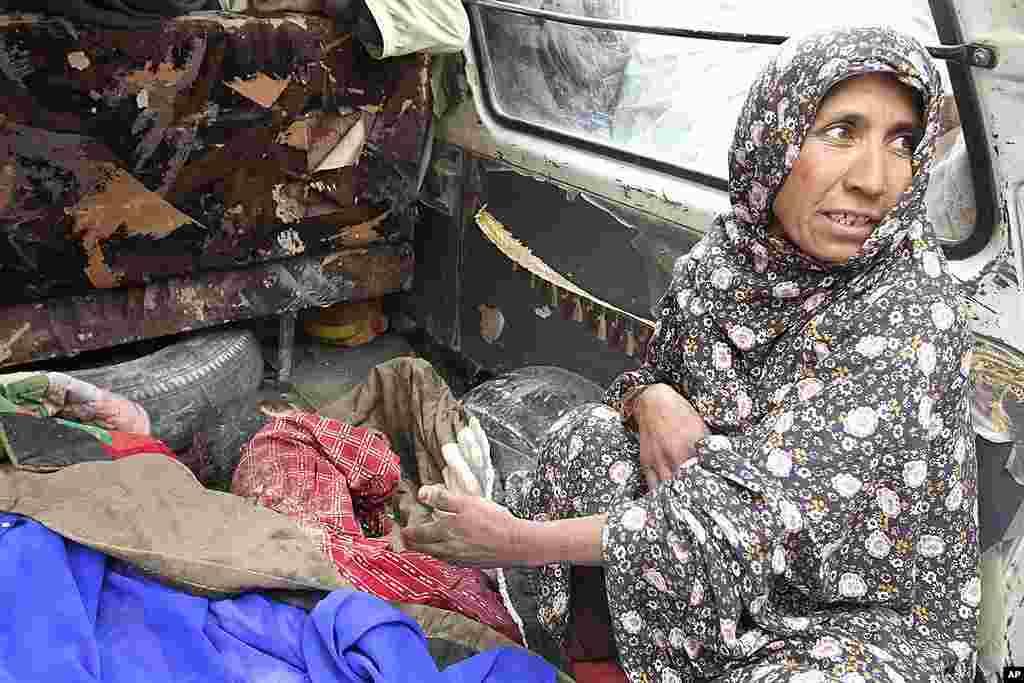 3月11号,阿富汗喀布尔以南坎大哈省本杰瓦尔区的安娜•古尔指着被她孙子的尸体。(AP)