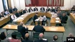 Rupert Murdoch y su hijo James, de espaldas en la imagen, durante una audiencia en el Parlamento británico.
