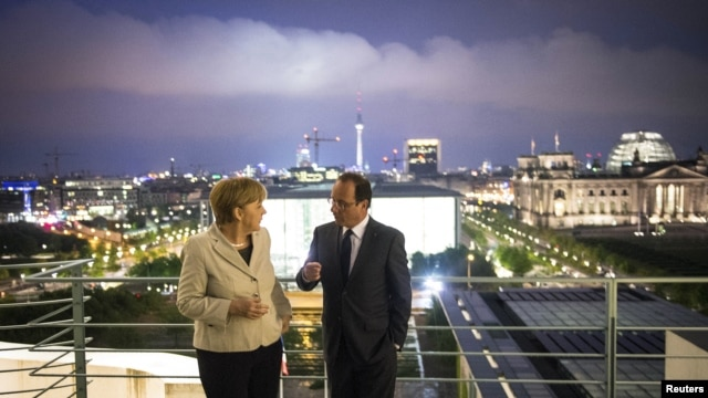 German Chancellor Angela Merkel and French President Francois Hollande speak after their joint news conference in the Chancellery in Berlin, May 15, 2012.