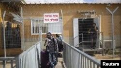 Des migrants africains, munis de bagages, quittent le centre de détention de Holot dans le désert du Néguev, dans le sud d'Israël, le 25 août 2015.