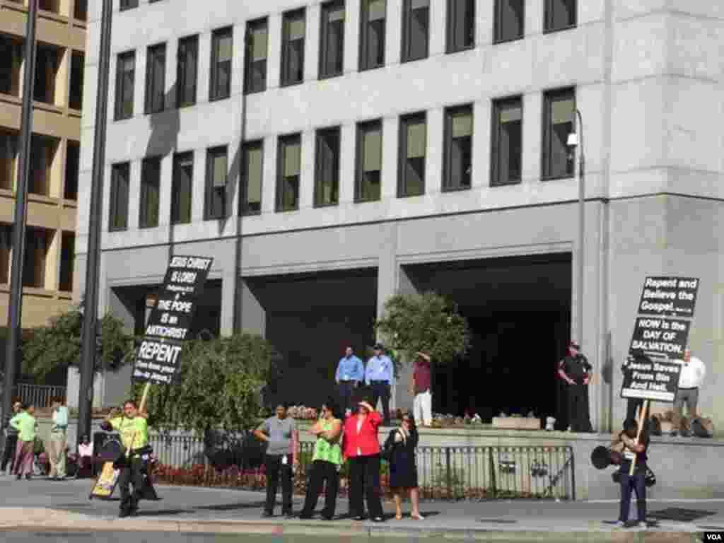 相较于白宫南草坪一万多名民众的欢迎,白宫外的抗议者举起标语,并和天主教支持者隔街对骂。 (美国之音张蓉湘拍摄)