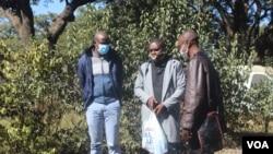 Les journalistes Samuel Takawira et Frank Chikowore aux côtés d'un inspecteur de police devant un tribunal à Harare, Zimbabwe, le 23 mai 2020. (Columbus Mavhunga/VOA)