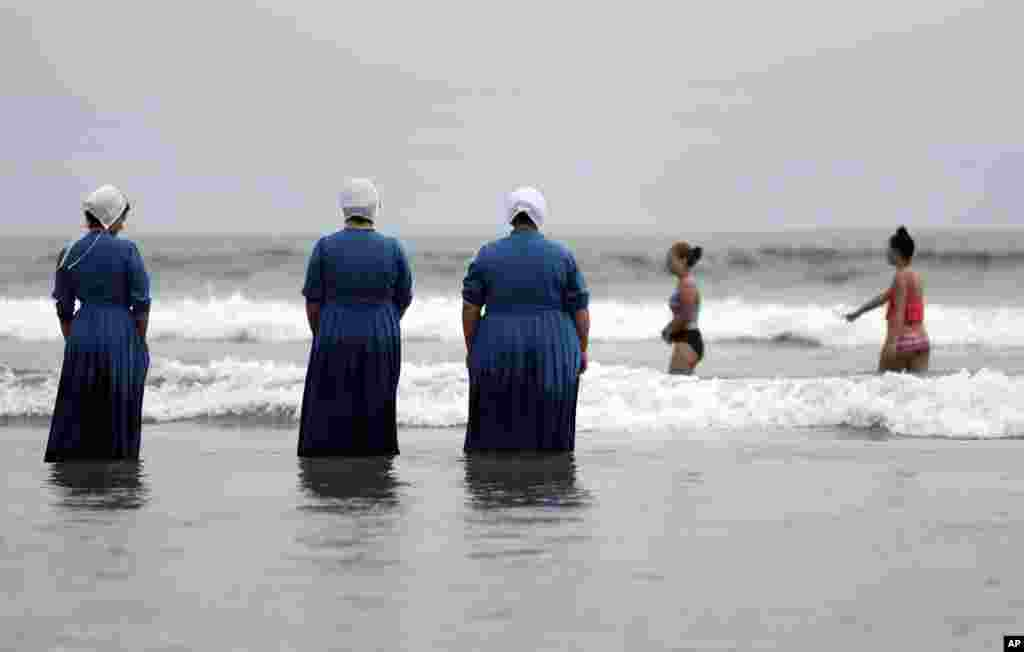 Rosa Graber, third from left, and Margerie, Steury, second from left, Joanne Steury, left, look on as they touch Pacific Ocean waters in Coronado, California, for the first time during a family trip from their Amish community in Michigan, June 9, 2016,