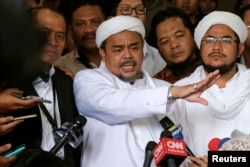 Leader of Islamic Defenders Front (FPI) Habib Rizieq (center) talks to reporters at a court after the blasphemy trial of Jakarta's incumbent governor Basuki Tjahaja Purnama, also known as Ahok, in Jakarta, Indonesia, Feb. 28, 2017.