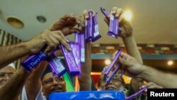Members of Malaysian Muslim Wholesalers and Retailers Association (MAWAR), a non-governmental organization, throw Cadbury chocolate products into a dustbin as a protest and officially announced their boycott of Cadbury products, after their news conferenc