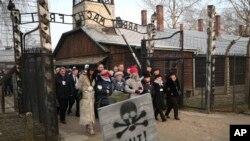 Президент Польши Анджей Дуда и почетные гости - бывшие узники, у входа в нацистский лагерь смерти Аушвиц. 27 января 2020 г.