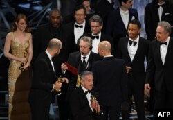 """La La Land"" producer Jordan Horowitz (2L) speaks to stage manager Gary Natoli (C), reading the winners card, after ""La La Land"" mistakenly won the best picture instead of ""Moonlight"" at the 89th Oscars on February 26, 2017 in Hollywood, California."