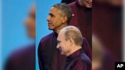El presidente ruso Vladimir Putin pasa frente al presidente Obama antes de tomarse la foto de familia de la APEC.