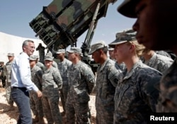 FILE - NATO Secretary General Jens Stoltenberg, second from left, of Norway meets with U.S. soldiers during his visit to view the U.S. Patriot missile system at a Turkish military base in Gaziantep, southeastern Turkey, Oct. 10, 2014.