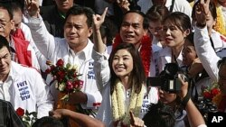 Opposition leader of Phue Thai party, Yingluck Shinawatra, center, flashes a number one sign as she arrives for the registration of constituency candidates competing in upcoming general election in Bangkok, May 24, 2011.