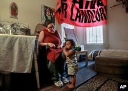 FILE - Franki Velez looks at her son Ashoka Little, 1, in their home in Oakland, California, Feb. 17, 2017. An Iraq War veteran who says she is on disability for Post Traumatic Stress Disorder, Velez is a full-time activist who is simultaneously cheered by and worried about the post-Trump infusion of more traditional liberals eager to protest.