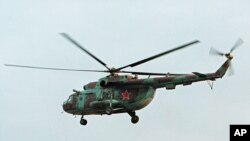 FILE - In this in this Sept. 18, 2002 file photo a Mi-8 helicopter flies over the Chechen regional capital Grozny, Russia. A helicopter similar to the one pictured has been shot down in Syria and Russian President Vladimir Putin's spokesman says all people aboard it have been killed, Aug. 1, 2016.