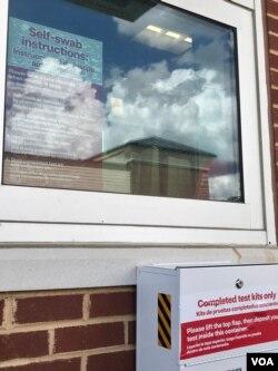新冠病毒得来速检测站。医护人员在玻璃窗后用对讲机指示,右下为检测小包搜集箱。 (美国之音黄耀毅拍摄)
