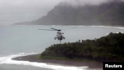 FILE - Australian helicopter flies low across the Weathercoast of the Solomon Islands.