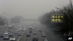 "Vehicles drive along a road with a traffic sign reading ""Visibility low, slowdown the speed"" on a heavily polluted day in Beijing, Monday, Nov. 30, 2015."