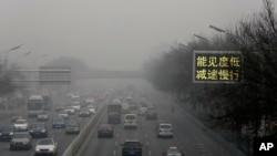 "Vehicles drive along a road with a sign reading ""Low visibility, slow down"" on a heavily polluted day in Beijing, Nov. 30, 2015."