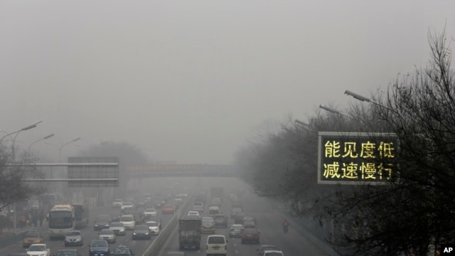 "FILE - Vehicles drive along a road with a traffic sign reading ""Visibility low, slowdown the speed"" on a heavily polluted day in Beijing, Monday, Nov. 30, 2015."