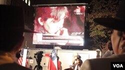 Con una mano en el corazón y la otra izando la bandera, algunos chilenos no pudieron contener las lágrimas al cantar el himno nacional.