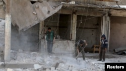 Residents remove debris after an airstrike on the rebel held al-Maysar neighborhood in Aleppo, Syria, April 11, 2016.