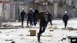 An anti-government protester throws a stone towards riot police during clashes in Daih, Bahrain, February. 14, 2013.