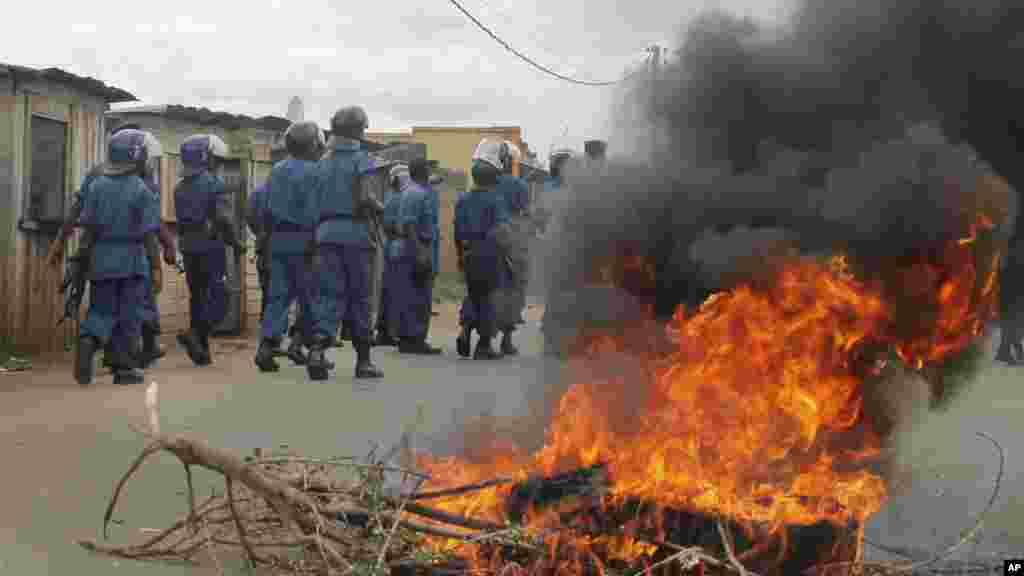La police anti-émeute burundaise, en patrouille, dépasse un pneu en flamme que des manifestant ont brulé sur une rue de la capitale Bujumbura, Burundi, dimanche26 avril 2015.