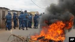 Polisi anti huru-hara Burundi melewati ban yang dibakar setelah bentrokan dengan demonstran oposisi di sebuah jalanan di ibukota Bujumbura, Burundi Minggu, 26 April 2015. Ratusan orang di Burundi berdemo setelah partai berkuasa menominasikan Presiden Pierre Nkurunziza untuk mencalonkan diri untuk masa jabatan ketiga. (AP Photo)