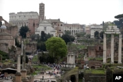 FILE - Tourists visit the ancient Roman forum and the Colosseum in Rome, April 17, 2015.