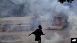 Amidst tear gas, a young man carries stones during a protest in Port-au-Prince, Haiti, September 14, 2011.