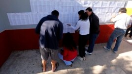 Citizens look for their names outside a public school before voting in nationwide congressional elections in Buenos Aires October 27, 2013.