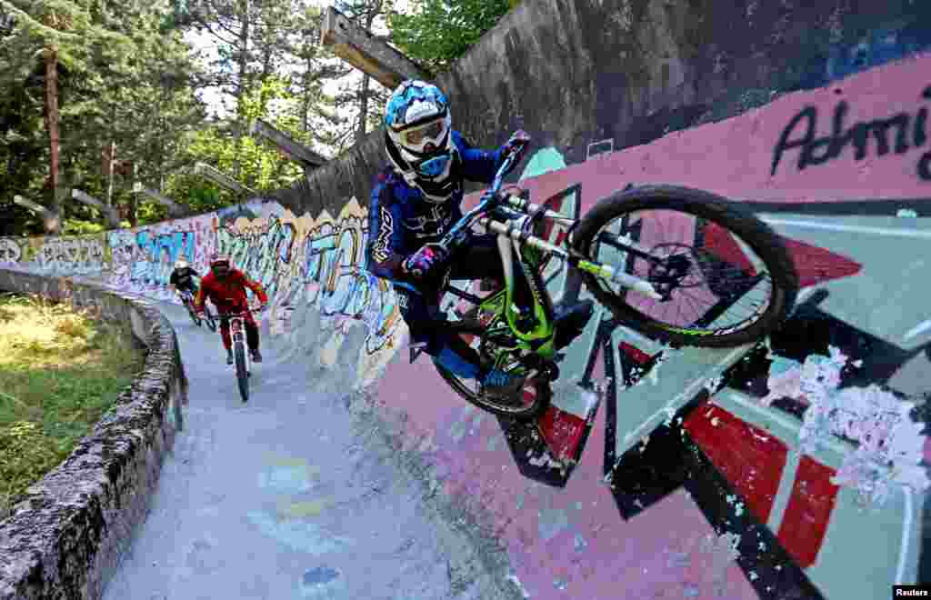 Downhill bikers Kemal Mulic (C), Tarik Hadzic (L) and Kamer Kolar train on the disused bobsled track from the 1984 Sarajevo Winter Olympics on Trebevic mountain near Sarajevo, Bosnia and Herzegovina, Aug. 8, 2015. Abandoned and left to crumble into oblivion, most of the 1984 Winter Olympic venues have been reduced to rubble by neglect as much as the 1990s conflict that tore apart the former Yugoslavia.