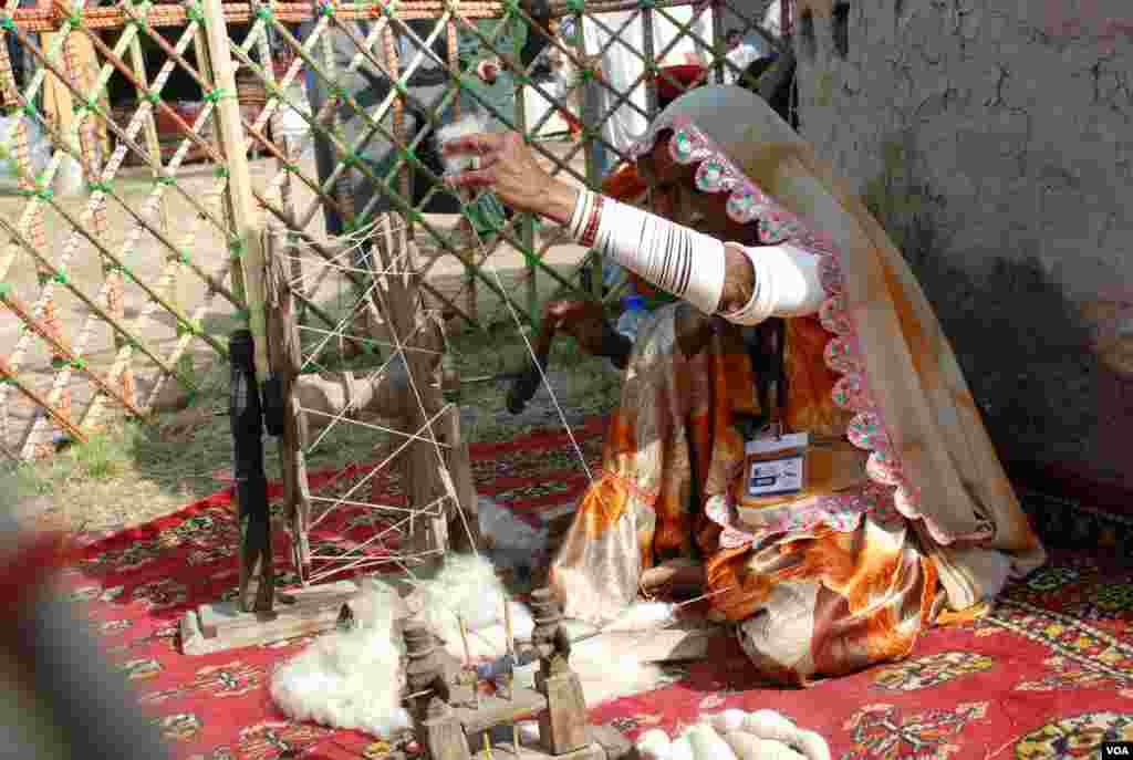 وادی مہران سے تعلق رکھنے والی خاتون روایتی چرخے پر سوت کات رہی ہے۔