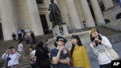 6月15日﹐中國遊客在紐約金融區遊覽拍照。